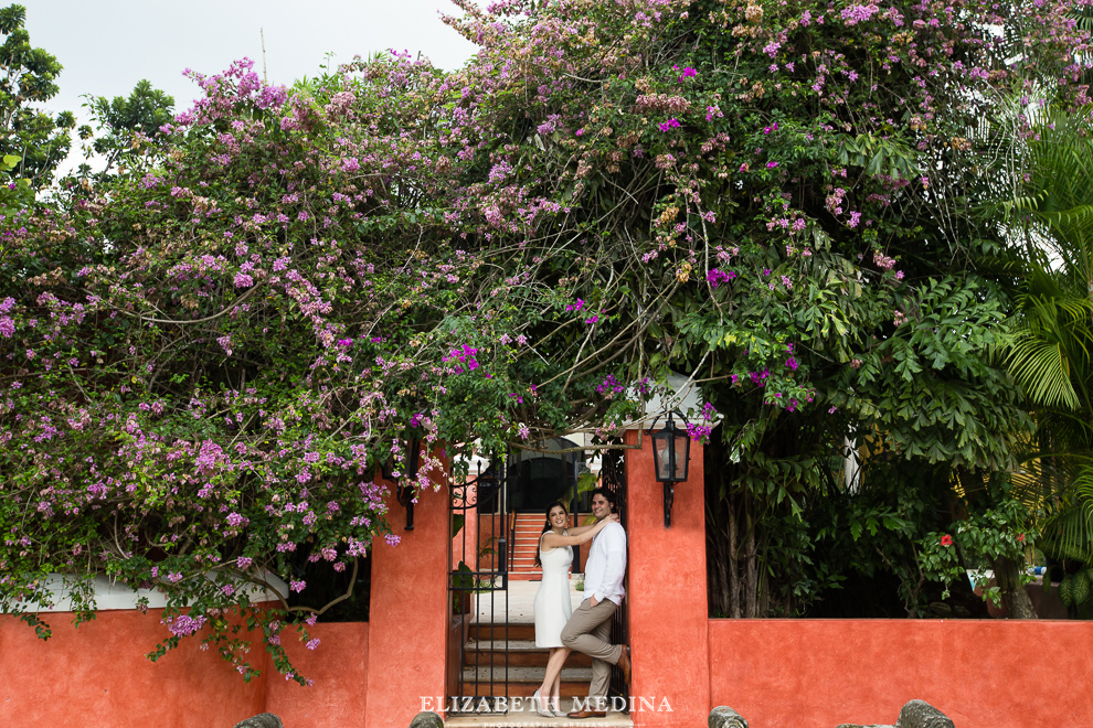 engaged couple surrounded by bouganvillia and a bright orange wall in Mexico